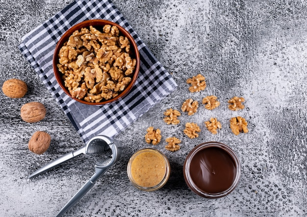 Вид сверху грецкие орехи в миску, щелкунчик и ореховое масло на деревянной горизонтали