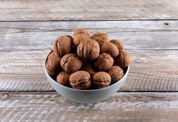 Вид сверху грецкие орехи в мисках на деревянной горизонтали