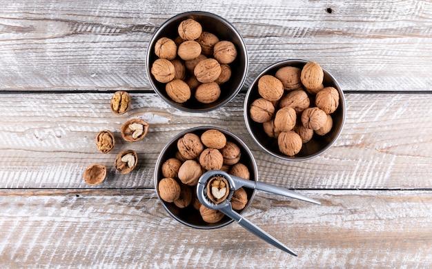 Вид сверху грецкие орехи в мисках с щелкунчиком на деревянной горизонтали