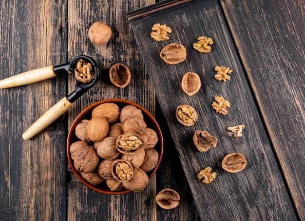 Вид сверху грецкие орехи в миску и щелкунчик на деревянной горизонтали