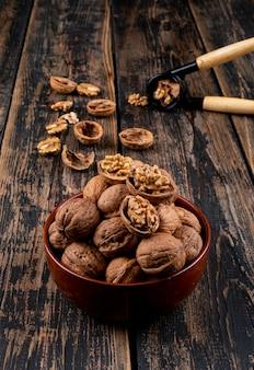 Вид сверху грецкие орехи в миску и щелкунчик на деревянной вертикали