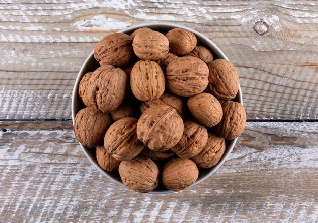 Вид сверху грецкие орехи в миску на деревянные горизонтальные