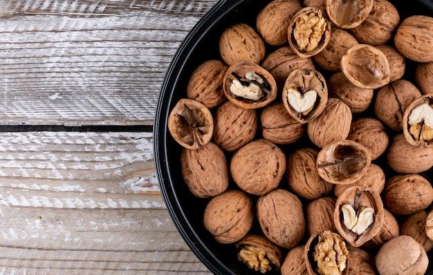 Вид сверху грецкие орехи в миску с копией пространства на деревянные горизонтальные