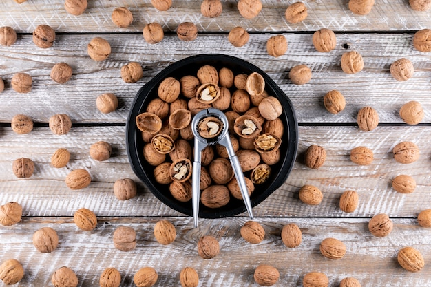 Вид сверху грецкие орехи в миску с щелкунчиком на деревянной горизонтали