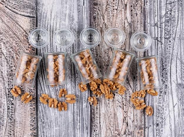 Вид сверху грецкие орехи в банки на деревянные горизонтальные