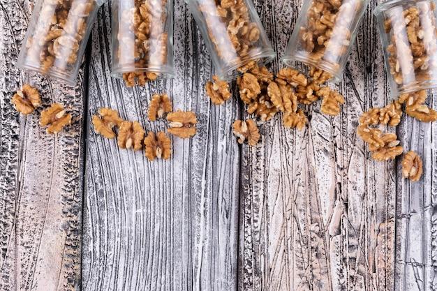 Вид сверху грецкие орехи в банках с копией пространства на деревянные горизонтальные