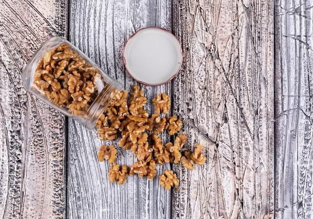 Вид сверху грецкие орехи в банке на деревянные горизонтальные