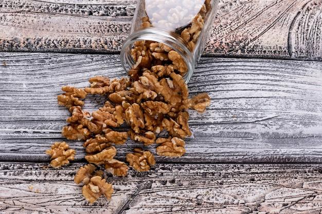Вид сверху грецкие орехи в банке на деревянный стол горизонтальный