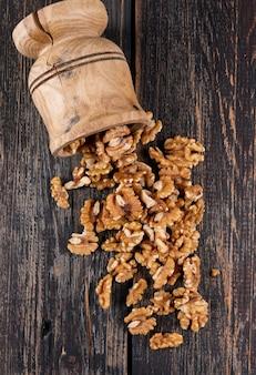 Вид сверху грецкие орехи в деревянной ступке на деревянной вертикали