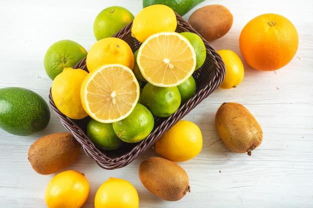 Свежие лимоны в корзине в окружении цитрусовых на белом деревянном