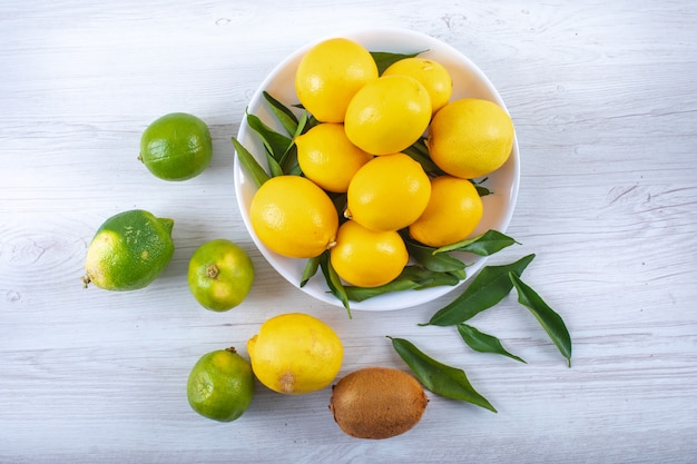 木のテーブルに葉トップビューで新鮮なレモン