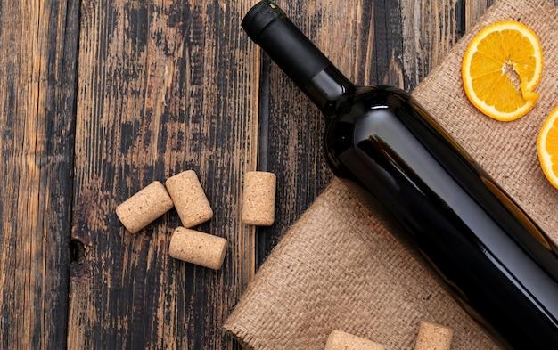 暗い木製の水平にコピースペースと荒布を着た平面図ワインボトル
