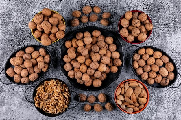 Вид сверху много грецких орехов в корзинах и мисках на деревянный стол горизонтальный