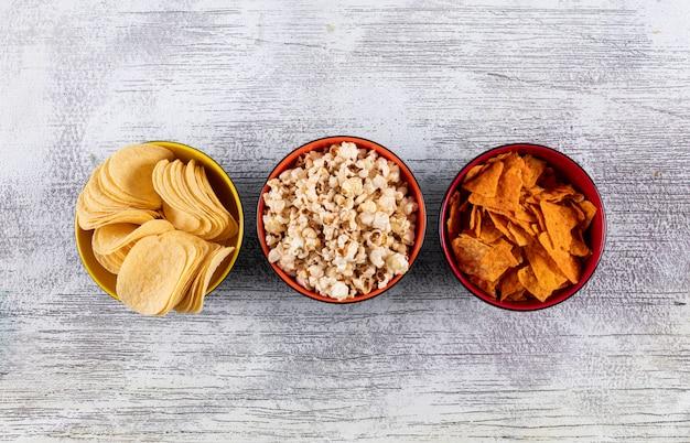 Вид сверху чипсов и попкорна в мисках на белой деревянной горизонтали