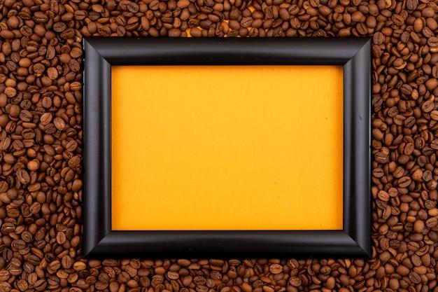 Черная рамка в окружении жареных кофейных зерен