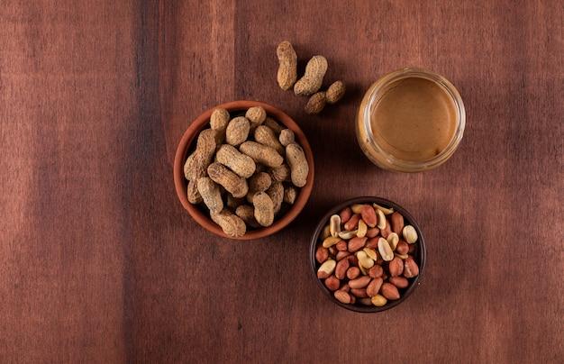Вид сверху сырой и очищенный арахис в миску и арахисовое масло на коричневой горизонтальной
