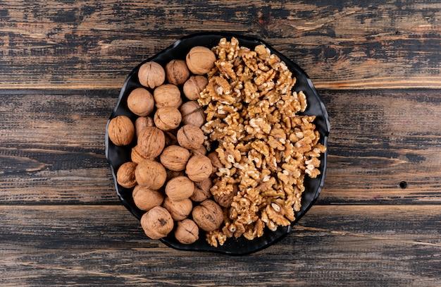Вид сверху шелушеные и сырые грецкие орехи в черной тарелке на деревянной горизонтали