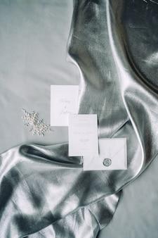 装飾と灰色の織り目加工の背景が付いている布の上の結婚式招待状のセット。上面図。