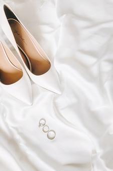 白い背景の上のかかとでトップビューの結婚指輪。垂直