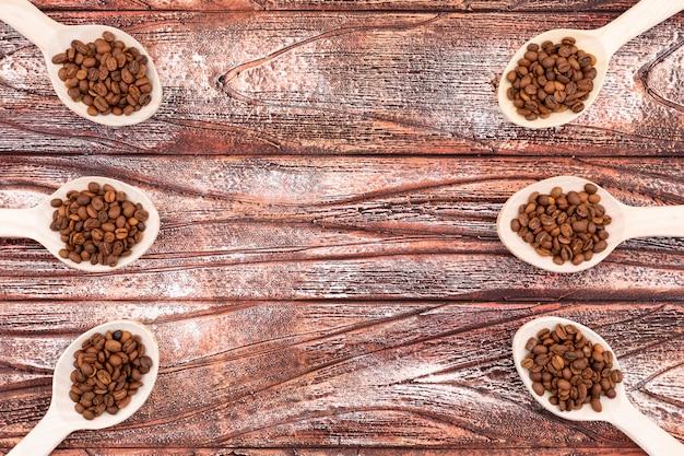 木の表面にコピースペースを持つ木製のスプーンでコーヒー豆