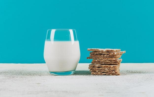 Набор вафли и стакан молока на синем фоне. вид сверху.