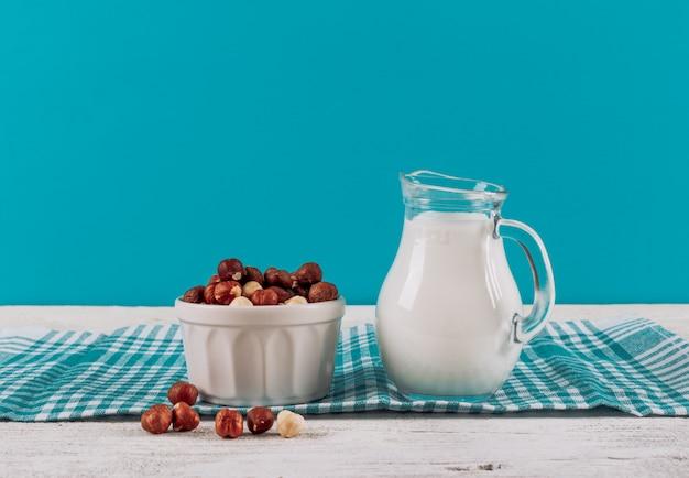 Графин молока вид сбоку с миску миндаля на фоне белой деревянной и синей ткани. горизонтальное пространство для текста