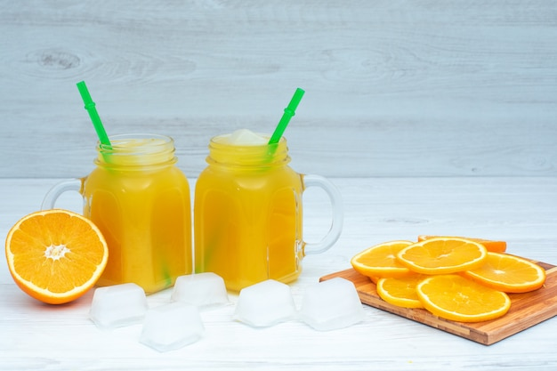 Апельсиновый напиток с кубиками льда на поверхности дерева