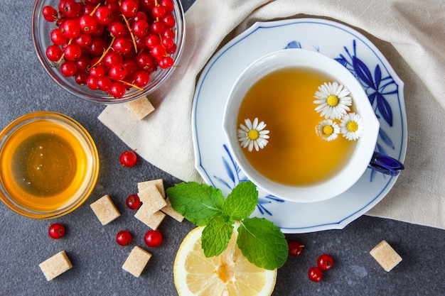 ボウルトップビューで砂糖、葉、レモン、スグリとカモミールティーのカップ