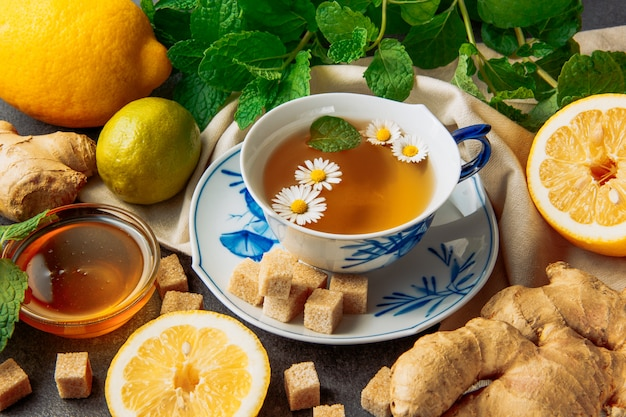 Чашка чая из ромашки с лимонами, имбирь, кубы желтого сахарного песка, мед в стеклянной посуде и зеленые листья в блюдце на фоне серых и кусок ткани, крупным планом.