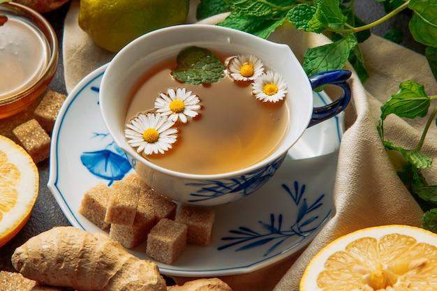 Чашка чая из ромашки с кусочками лимона, имбиря, коричневого сахара кубиками и зелеными листьями в блюдце на фоне серого и пикника ткани, крупным планом.