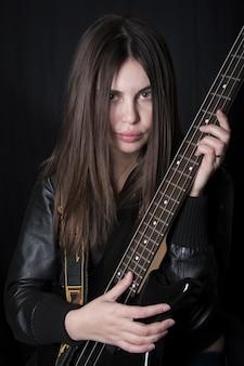 電気ベースを演奏する黒いジャケットで美しい女性