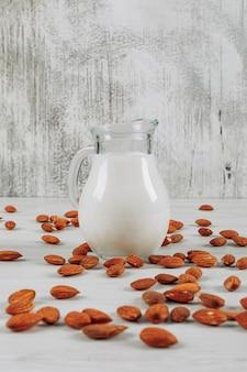 Некоторый графин молока с миндалинами на белой деревянной предпосылке, взгляде со стороны.