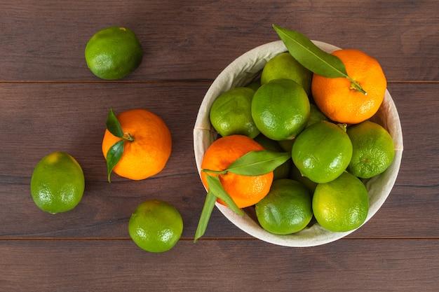 Корзина с зелеными лимонами и апельсинами на коричневой деревянной поверхности