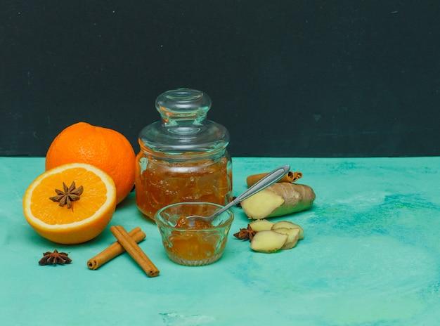Апельсины с вареньем в блюдце, имбирь и ломтики вид сбоку на голубой текстурированной и темный