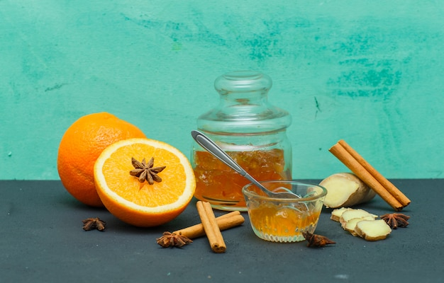 Апельсины с вареньем в блюдце, имбирь и ломтики вид сбоку на голубой текстурированной поверхности