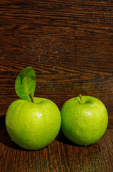 湾曲したダークウッドの葉と緑のリンゴを濡れています。側面図。