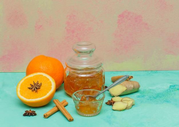 Вид сбоку апельсины с вареньем в блюдце, имбирь и кусочки на голубой текстурированной поверхности. горизонтальный