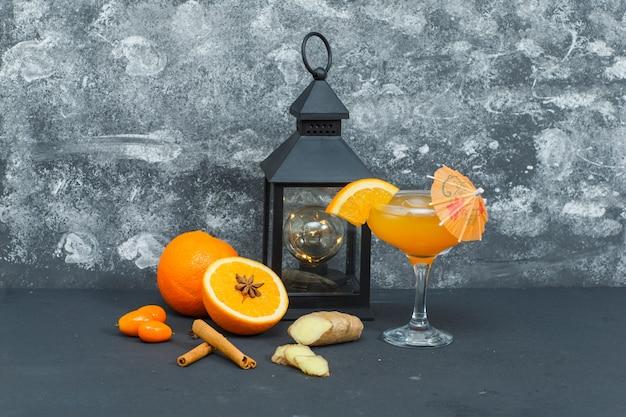 Некоторые апельсины с античный свет, сок в стакан, имбирь и кусочки на текстурированной поверхности, вид сбоку.