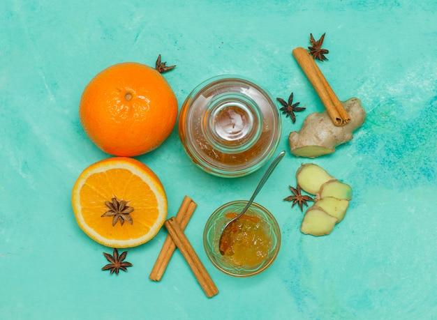 Некоторые апельсины с вареньем в блюдце, имбирь и кусочки на голубой текстурированной поверхности, вид сверху.