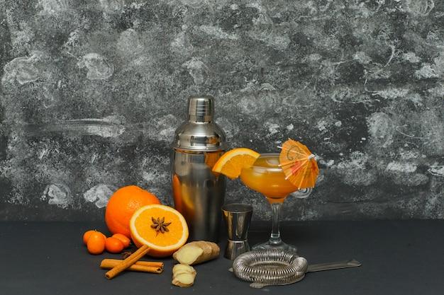 いくつかのオレンジジュース、ガラス、魔法瓶、生姜、織り目加工の表面のスライス、側面図。