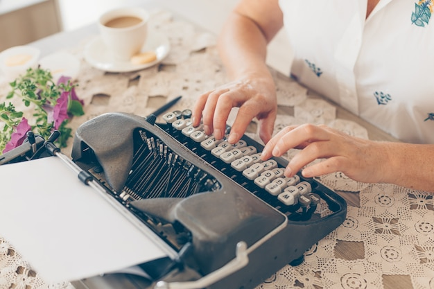 昼間に白いシャツの家の中でタイプライターで入力する年上の女性