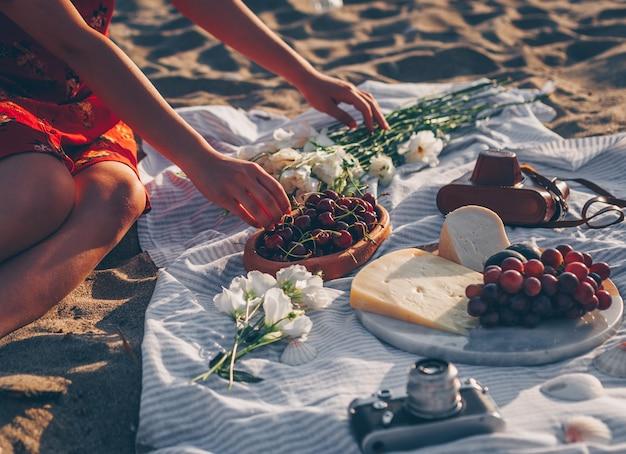 ビンテージカメラ、花、チーズ、ビーチで果物と木の板でさくらんぼを拾う女性