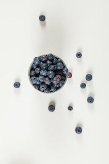 Острые ягоды черники в мини-ведре на белой поверхности