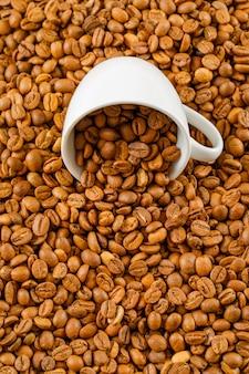 白いカップに散らばったコーヒー豆。ハイアングル。