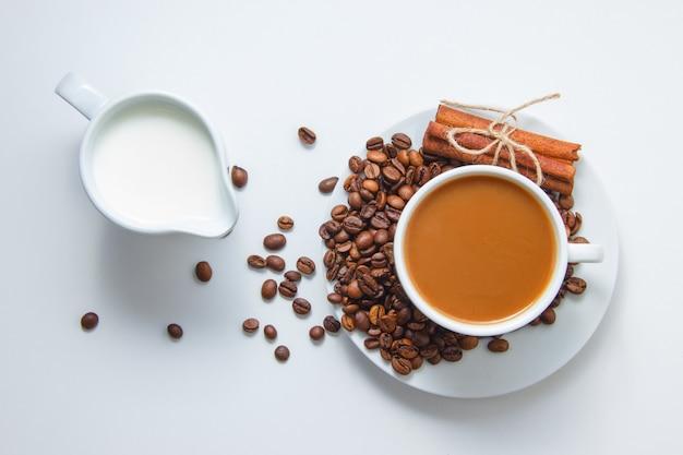 Вид сверху чашка кофе с кофейными зернами и сухой корицей на блюдце и с молоком, на белой поверхности