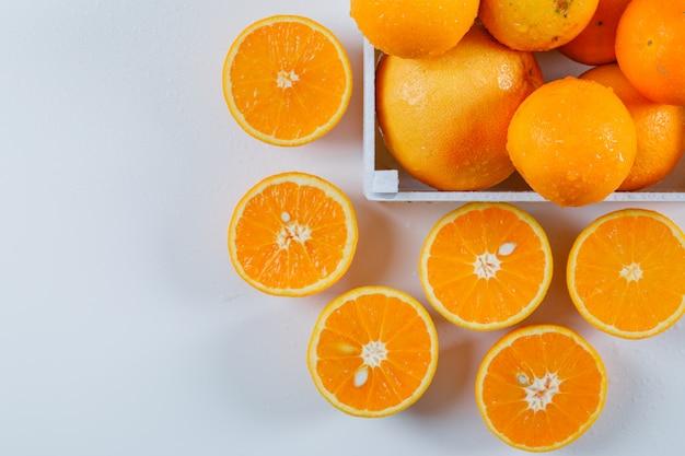Влажные апельсины с половинками в миску белого прямоугольника на белой поверхности. высокий угол обзора.