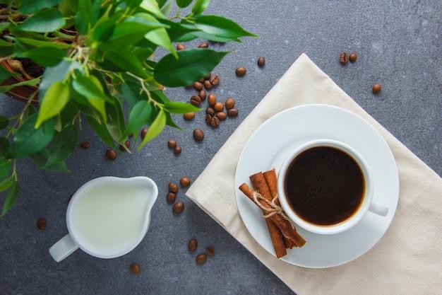 灰色の表面に乾燥したシナモン、植物、牛乳とコーヒーのカップを平面図します。横型