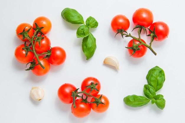 Взгляд сверху пуков томатов с чесноком и листьев на белой предпосылке. горизонтальный