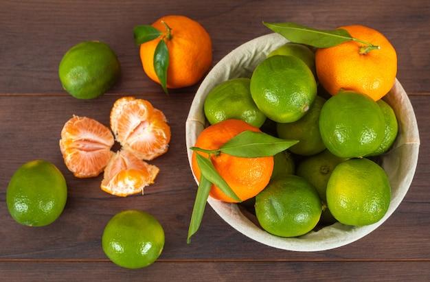 Мандарины сверху в корзине и зеленые лимоны на поверхности дерева
