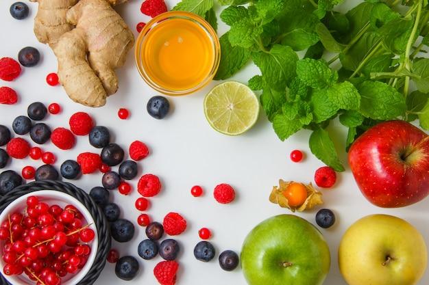 Вид сверху малина с медом, яблоки, черника, красная смородина, лимон, имбирь, листья мяты на белой горизонтальной поверхности